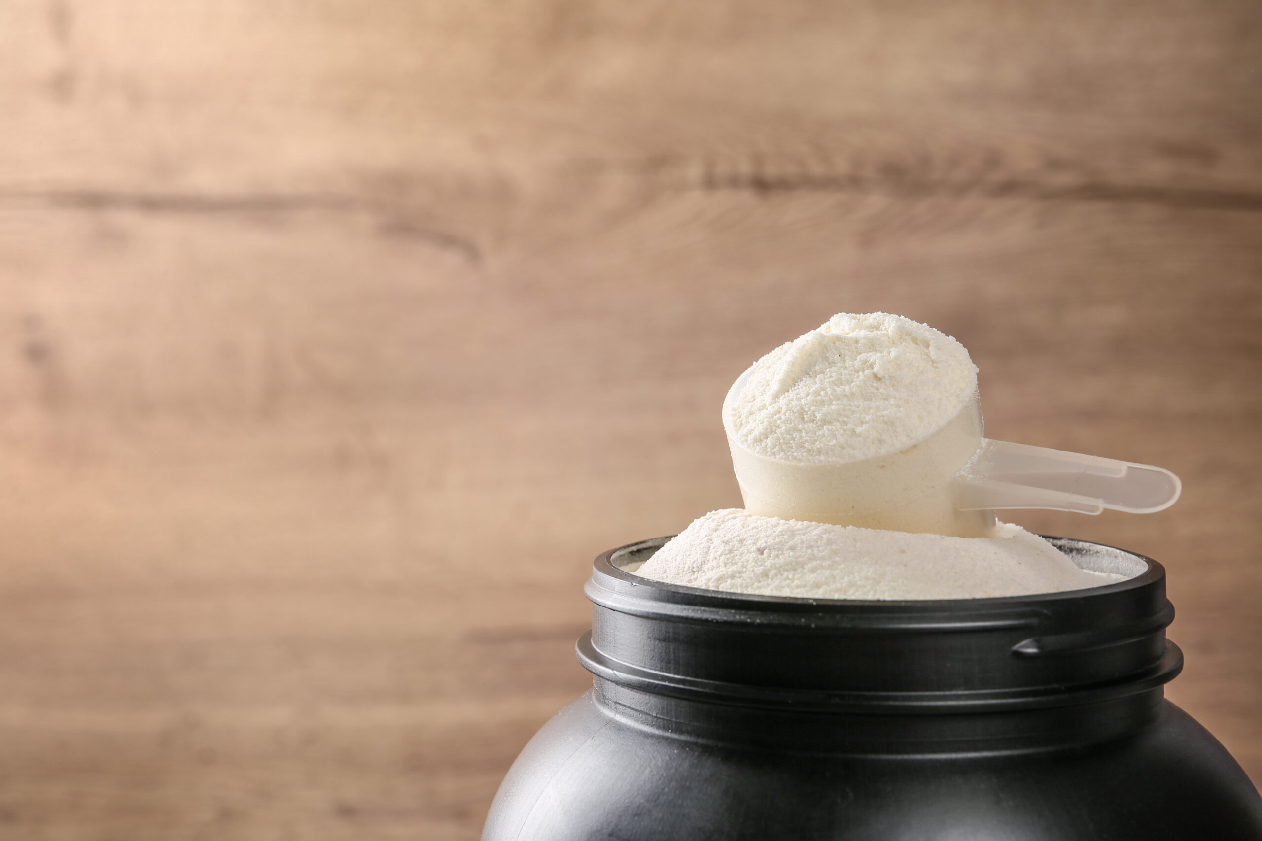 Black jar with measuring scoop of protein powder against wooden background. Space for text