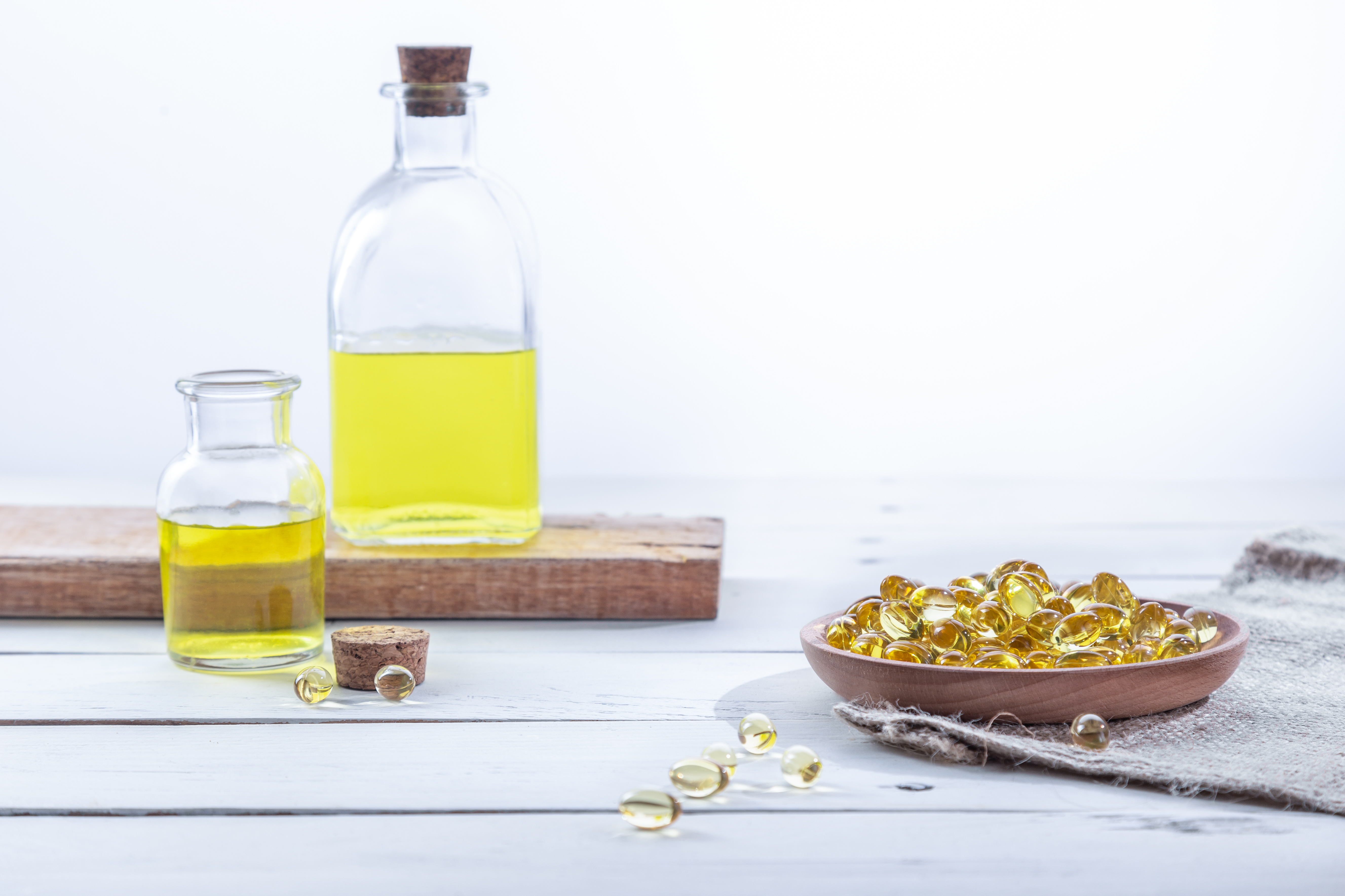 Evening primrose oil in capsules and in bottles, on a white wooden base. Health care concept.
