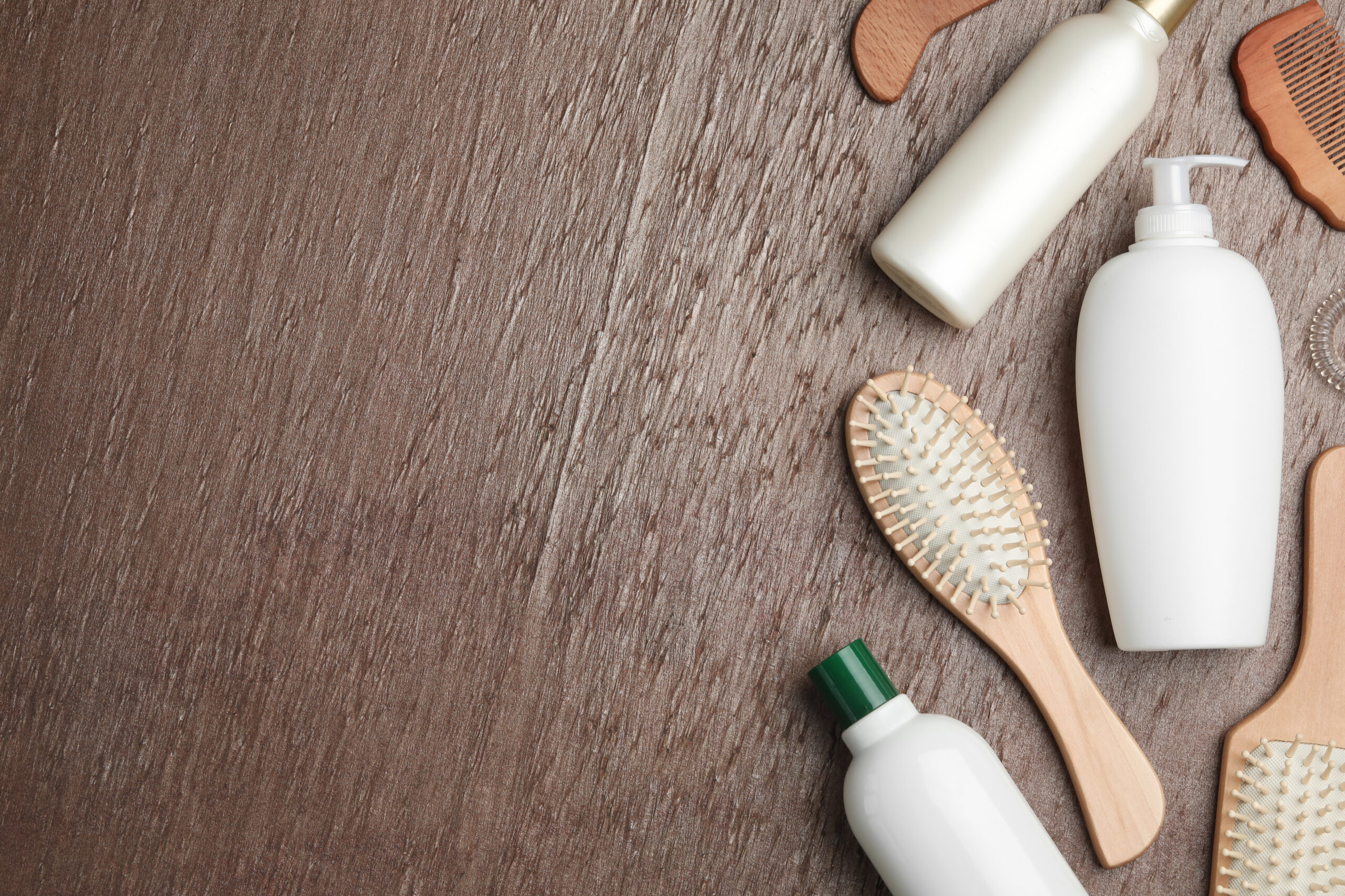 Flat lay composition with hair cosmetic products and tools on brown background. Space for text